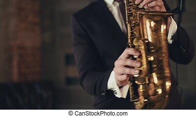 Saxophonist in black suit play jazz on golden saxophone with microphone. Music.