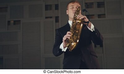 Saxophonist in black suit play on golden saxophone with microphone. Jazz music