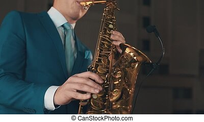 Saxophonist in blue suit play jazz on golden saxophone at stage. Music. Artist