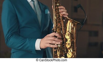 Saxophonist in blue suit play jazz on golden saxophone on stage. Elegance.
