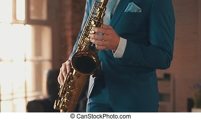 Saxophonist in blue suit play jazz on golden saxophone with microphone. Elegance