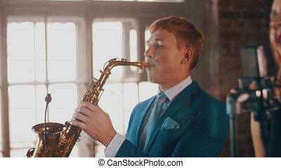 Saxophonist in blue suit play on golden saxophone. Live performance. Jazz.