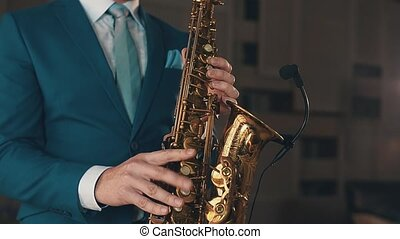 Saxophonist in blue suit playing on golden saxophone at stage. Elegance. Jazz