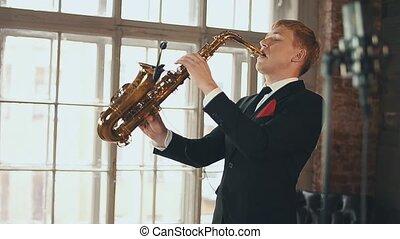 Saxophonist in dinner jacket performing on stage. Jazz artist. Microphone.
