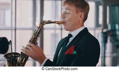 Saxophonist in dinner jacket performing on stage of restaurant. Jazz music.