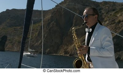 Saxophonist in white suit play jazz on golden saxophone at...