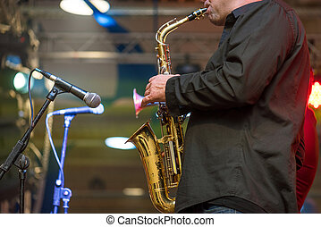 Saxophonist playing a saxophone. - Musicial music live band...