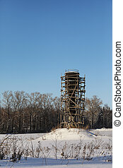 Scaffold around the water tower in field in front of forest