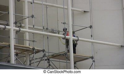scaffold builders - Construction worker building scaffolding...