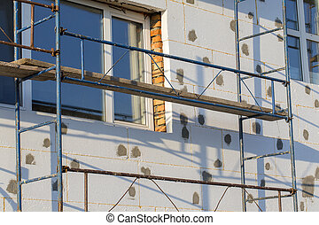 Scaffold on house, renovation. House for renovation with the scaffolding for workers on building
