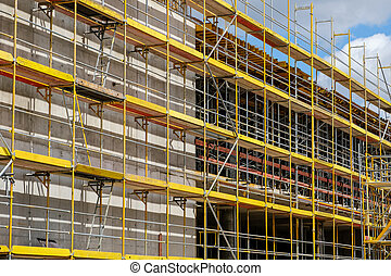 scaffolding on new building facade , construction site with framework on buiding