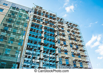 Scaffolding on renovation of glass facade house bright sunny day blue sky