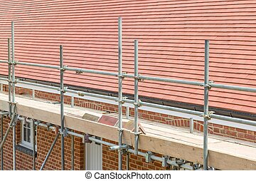Scaffolding outside a UK house with a plain clay tile pitched roof