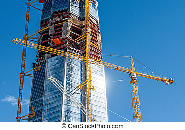 Scale active skyscraper building, glare from the sun on the windows, cranes against the blue sky.