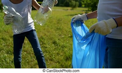 Scaled up look on children cleaning trash in park -...