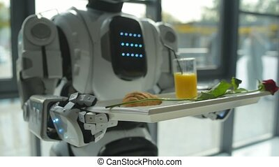 Scaled up look on robot holding trey with breakfast -...