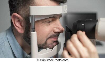Scaled up of bearded man undergoing eye examination - Slit...