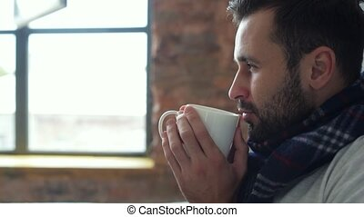 Scaled up of relaxed millennial guy in scarf drinking tea -...