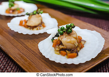 Scallops served on a shell.