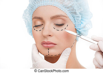 Scalpel near face. Portrait of beautiful young woman in medical headwear keeping eyes closed while doctors hands in gloves holding scalpel near her face