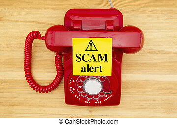 Scam alert message on a sticky note on a red old retro rotary phone