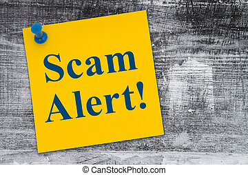 Scam Alert message on a yellow sticky note on weathered wood