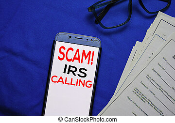 SCAM! IRS Calling text on Smart Phone isolated on office desk.