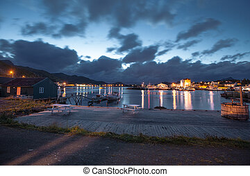 Scandinavian house and mirror lake with view to city and sea in the Norway at summer at sunset