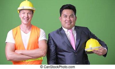 Scandinavian man construction worker and Asian businessman...