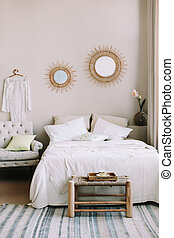 Scandinavian modern cozy interior. Wide bed with pillows, armchair and decorations in bedroom.