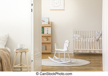 Scandinavian nursery with white wooden crib, round carpet and rocking horse in the middle, real photo with copy space