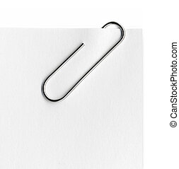 Scanned metal paper clip and paper on white background.