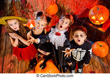 scare each other - Cheerful children in halloween costumes ...
