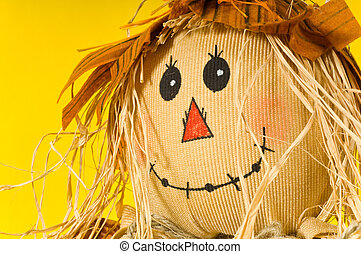 Closeup of scarecrow on yellow background