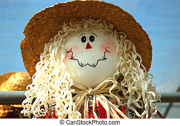 The smiling face of a harvest scarecrow doll.