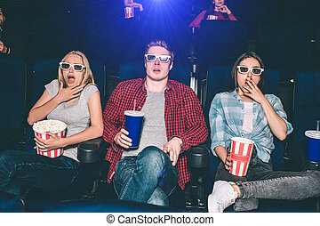 Scared and frightened people are watching movie in cinema. They are sitting and looking straight forward. Everyone has a basket of popcorn or a cup with coke. They are not alone in the hall.