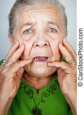 Scared and worried senior woman with wrinkles - Portrait of...