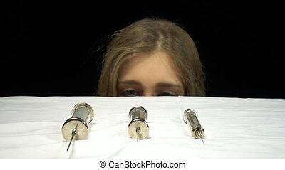 Scared blond girl and syringe