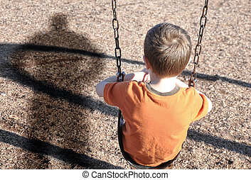 A young boy is sitting on a swing set and looking at a shadow figure of a man or bully at a playground. Use it for a kidnap or defense concept.