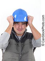 Scared builder holding hat
