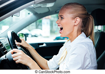Scared business woman driving her car
