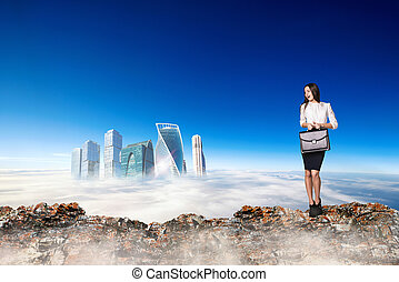 Scared business woman stands on the edge of mountain range.