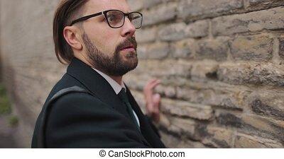 Scared businessman creeping near brick wall - Scared bearded...