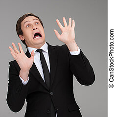 Scared businessman. Terrified young businessman looking up and gesturing while isolated on grey