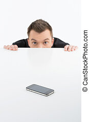 Scared businessman. Terrified young men looking out of the table with mobile phone on it