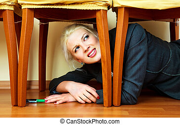 young attractive businesswoman hiding under the chair