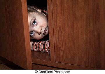 Scared child hiding - Scared child boy hiding in wardrobe