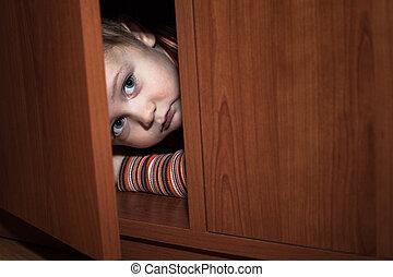 Scared child hiding - Scared child boy hiding in wardrobe