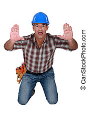 Scared construction worker with his hands up