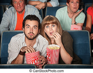 Scared Couple In Theater - Scared Caucasian couple eating...